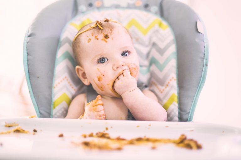 Bebé en la trona manchado de comida
