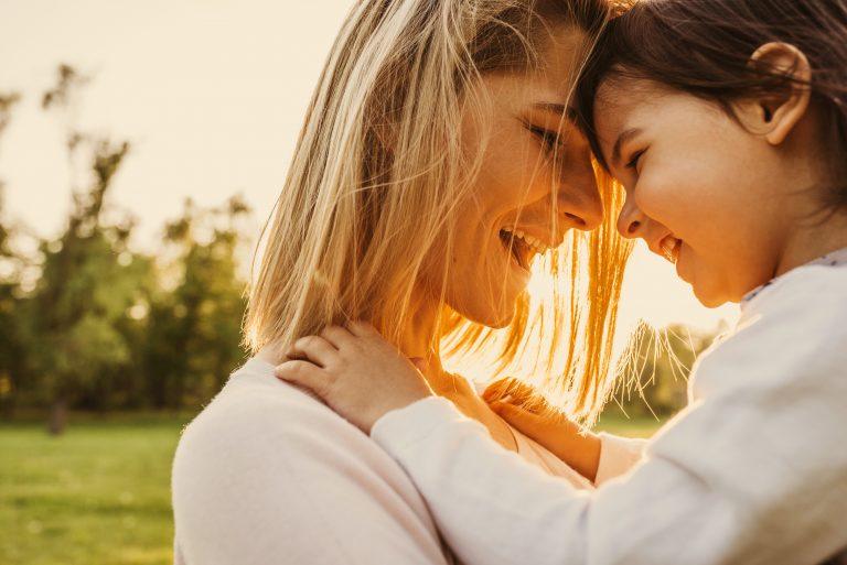 Madre e hija unen sus cabezas cómplices y sonriendo