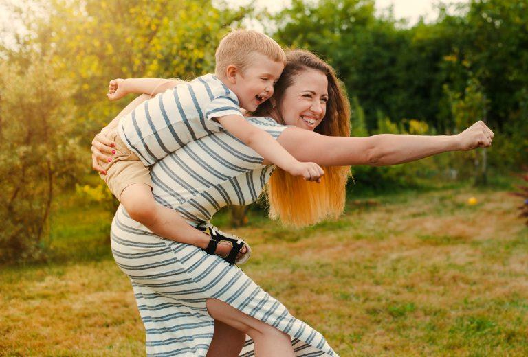 Madre e hijo, felices, juegan a ser superhéroes